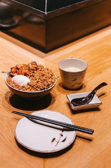 Frango yakitori rice bowl com carne de porco picada servido com ovo cozido no vapor chinês.