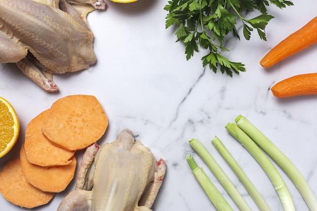 Frangos inteiros coquelet com vegetais crus prontos para cozinhar. cenouras, alho-poró; batata doce; salsa de cima. postura plana