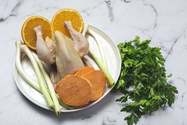 Frangos inteiros coquelet com vegetais crus prontos para cozinhar