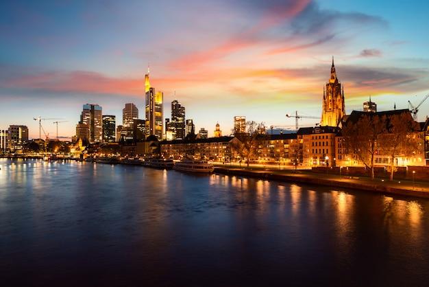 Frankfurt am main skyline urbana com arranha-céus de construção à noite em frankfurt, alemanha