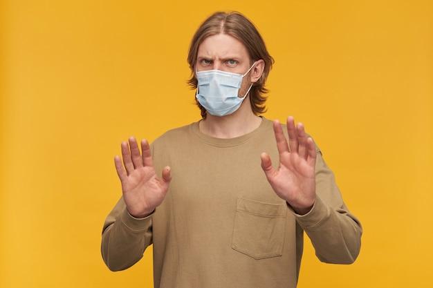 Franzindo a testa, cara barbudo bonito com penteado loiro. vestindo um suéter bege e máscara médica. afasta os braços, gesto protetor. isolado sobre a parede amarela