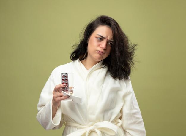 Franzindo a testa, jovem caucasiana doente vestindo um manto segurando um pacote de comprimidos médicos, um copo de água e um guardanapo, olhando para o lado isolado em fundo verde oliva