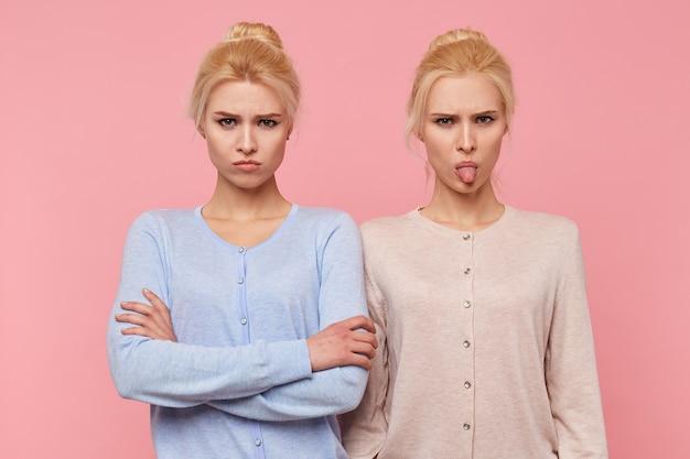 Franzindo a testa lindas jovens loiras gêmeas de mau humor, olhando para a câmera isolada sobre fundo rosa.