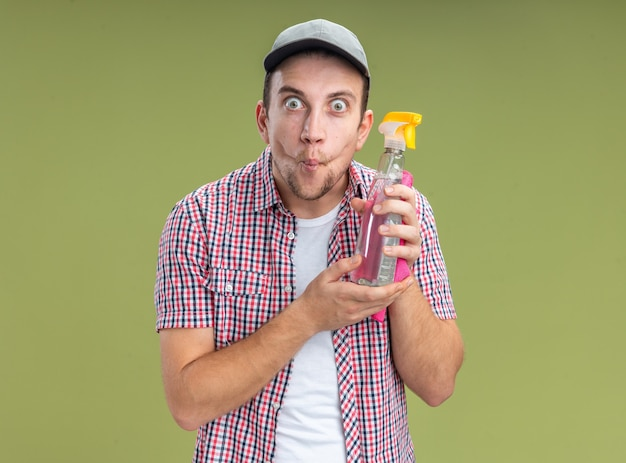 Franzindo os lábios jovem limpador usando boné segurando agente de limpeza com pano isolado na parede verde oliva