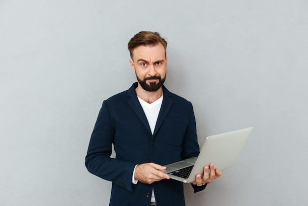 Franzir a testa homem sério no terno usando laptop isolado
