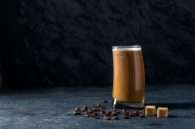 Frapê de café gelado em copo alto com açúcar e grãos de café
