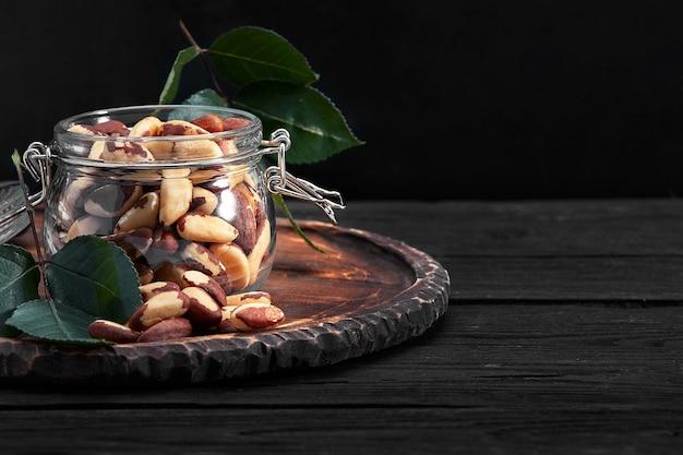 Frasco aberto cheio de castanhas do brasil perto de uma mesa escura