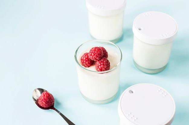 Frasco aberto com iogurte caseiro e framboesas sobre um fundo azul