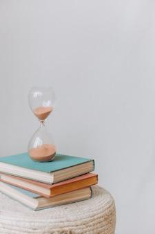 Frasco ampulheta com pilha de livros medindo a contagem regressiva do tempo