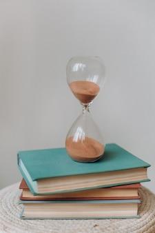 Frasco ampulheta com suporte retrô pilha de livros medindo a contagem regressiva do tempo