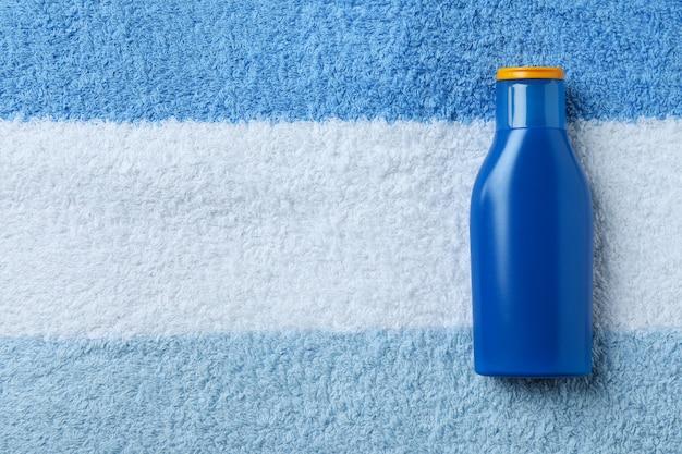 Frasco azul de protetor solar em fundo de toalha isolado