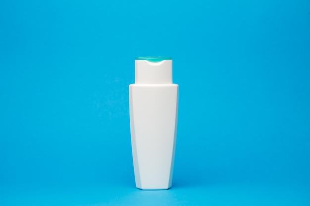 Frasco branco com creme, shampoo de cabelo, gel de banho, fundo azul isolado, beleza do corpo humano