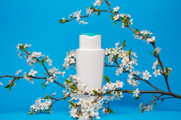 Frasco branco com creme, shampoo para cabelo, gel de banho, fundo azul isolado, beleza e juventude do corpo humano, árvore florida