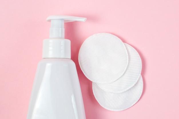 Frasco branco com gel para lavar e enxugar rostos, almofadas macias de algodão, água micelar para desmaquilhar, limpar a pele e tratamentos cosméticos em mesa rosa pastel.