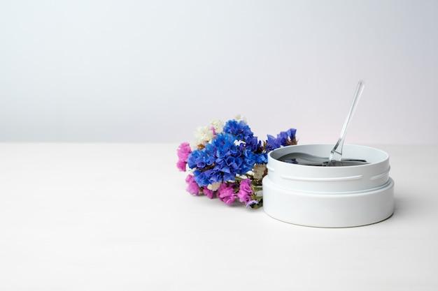 Frasco branco com manchas douradas e pinças na mesa branca com flores coloridas