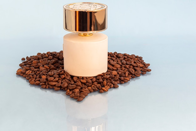 Frasco branco com perfume feminino. cercado por grãos de café em um espaço claro.