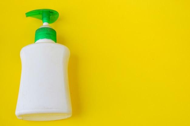 Frasco branco de desinfetante para as mãos isolado em fundo amarelo