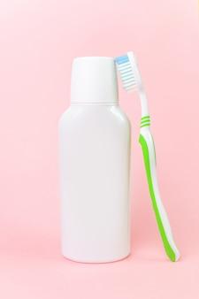 Frasco branco do colutório e escova de dentes no rosa pastel.