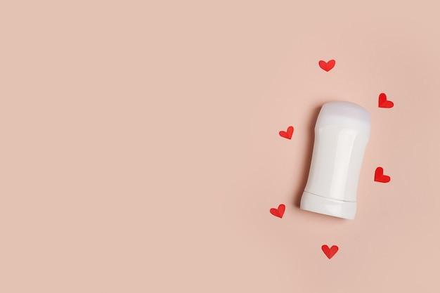 Frasco branco para maquete de design de produto desodorante em fundo rosa com corações vermelhos, conceito de cuidados com o corpo com amor. copie o espaço