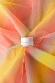 Frasco branco para produto de beleza em tecido de organza colorido arco-íris. maquete de loção creme hidratante para os olhos. conceito de higiene de cuidados de saúde