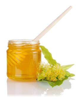 Frasco cheio com mel de tília, concha de mel e flores de limão isoladas no fundo branco.