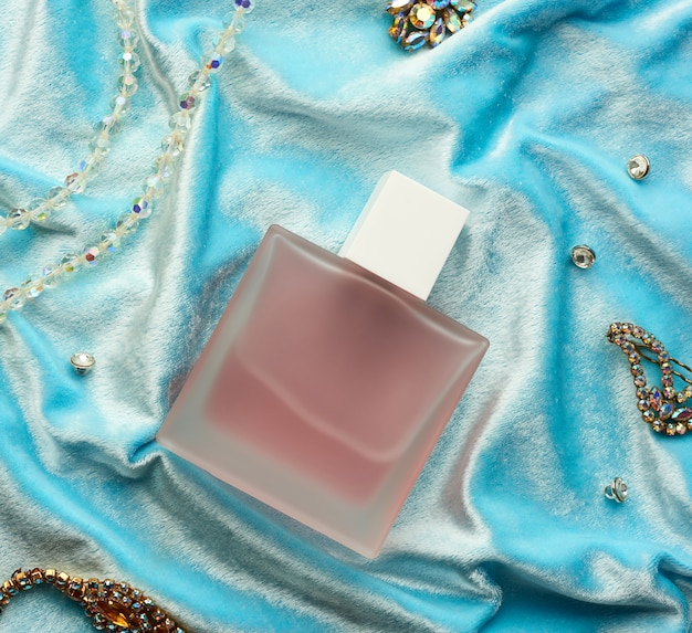 Frasco cheio rosa com perfume de vidro fosco sobre fundo azul