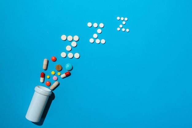 Frasco com diferentes tipos de pílulas para dormir com espaço livre para o texto de uma receita