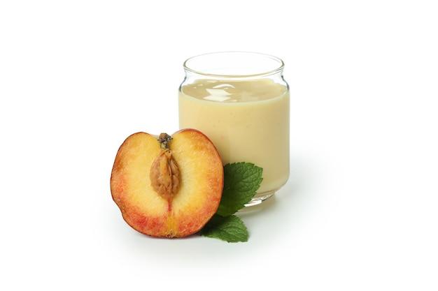 Frasco com iogurte de pêssego e ingrediente isolado no fundo branco