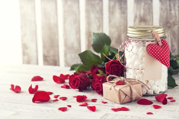 Frasco com marshmallow, presente e buquê de rosas. amor, doce ou