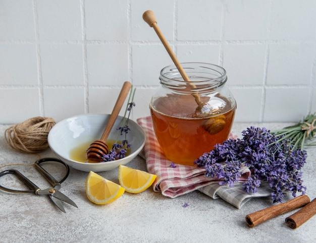 Frasco com mel e flores frescas de lavanda em um fundo de concreto