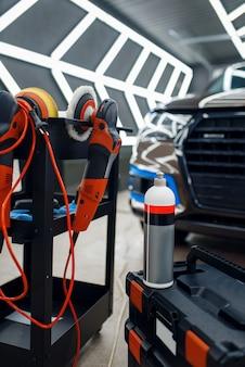 Frasco com polidor de proteção e polidora, detalhamento de carro, ninguém. instalação de revestimento que protege a pintura do automóvel de arranhões. veículo novo na garagem, ajuste automático