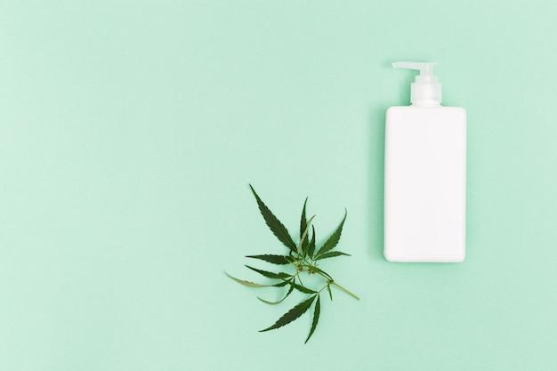 Frasco com produto cosmético, gel ou shampoo com óleo de cannabis em fundo de cor verde.