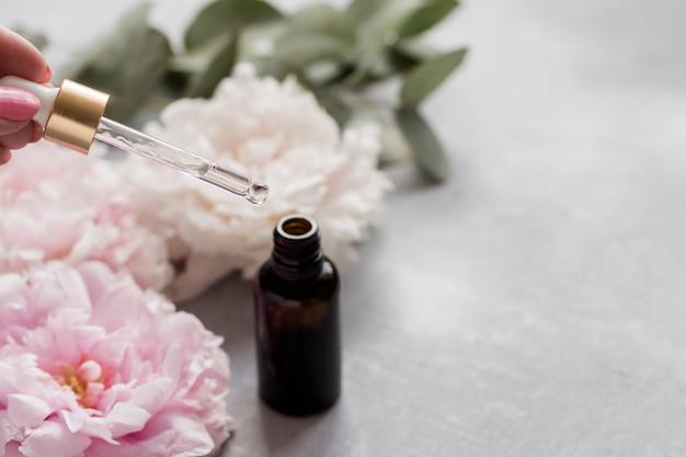 Frasco com soro cosmético e pipeta em um fundo de delicadas flores e ervas