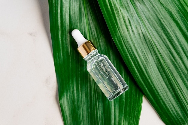 Frasco com soro na mesa de mármore, folha de palmeira verde na superfície
