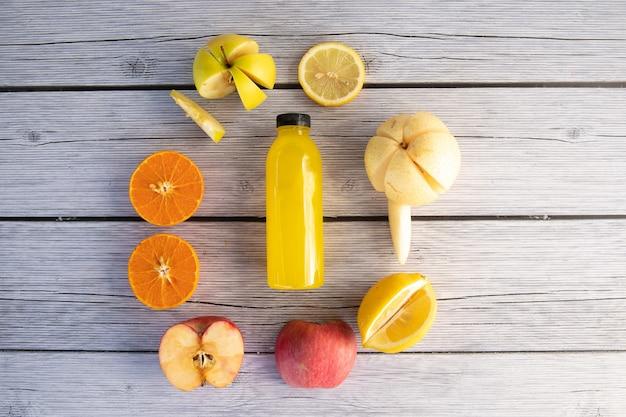 Frasco comprimido a frio de suco amarelo saudável em uma placa de madeira feita de laranja, maçã, pêra, limão e suco de frutas