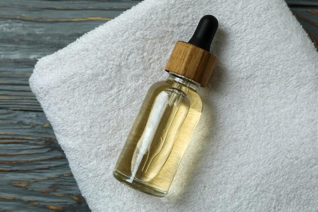 Frasco conta-gotas com óleo na toalha em fundo de madeira isolado