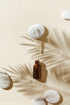 Frasco conta-gotas de soro ou colágeno líquido em fundo de areia com sombra de luz solar de folhas de palmeira