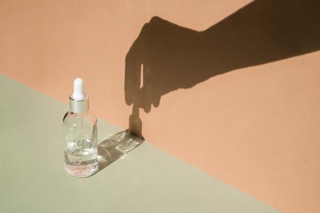 Frasco conta-gotas de vidro com sombra de mão na parede. tratamento corporal e spa. produtos de beleza naturais. eco creme, soro, frasco em branco para cuidados com a pele. óleo de massagem anticelulite. pipeta cosmética oleosa.