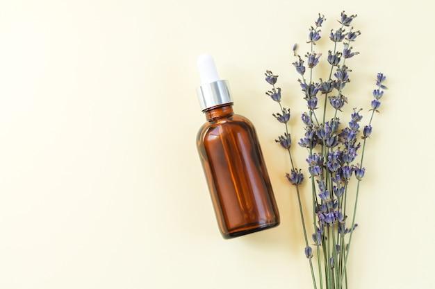 Frasco conta-gotas de vidro marrom com óleo orgânico de lavanda ou soro próximo a flores de lavanda secas, vista superior