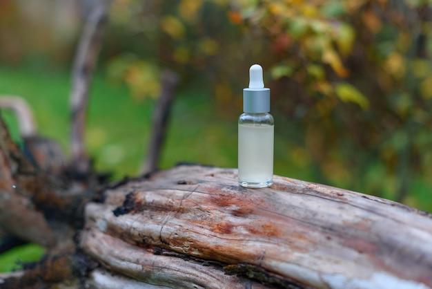 Frasco conta-gotas de vidro para óleo cosmético ou soro na casca de uma árvore