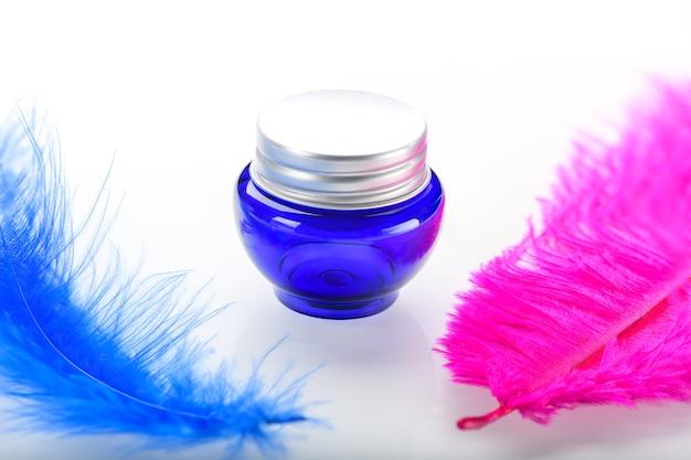 Frasco cosmético azul com duas penas decorativas de avestruz isoladas