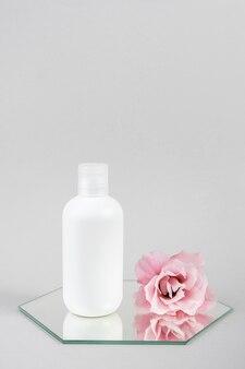 Frasco cosmético branco em branco e flor rosa no espelho, fundo cinza. maquete do conceito de beleza cosmética natural organic spa, vista frontal.