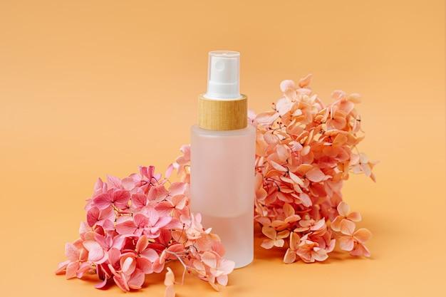 Frasco cosmético com flores cor de rosa em fundo pastel. conceito de beleza