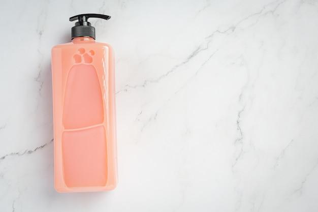 Frasco cosmético com shampoo de morango na superfície branca