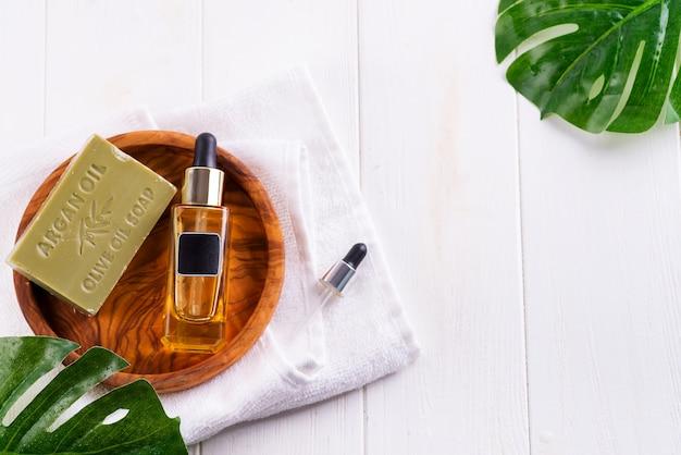Frasco cosmético com soro ou ácido hialurônico e sabão de oliva na placa de madeira, folha de palmeira, em uma toalha branca
