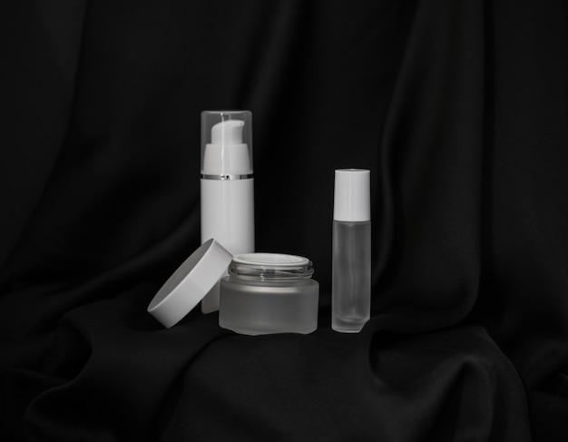 Frasco cosmético com tampa aberta. frasco cosmético e spray cosmético em fundo de tecido preto