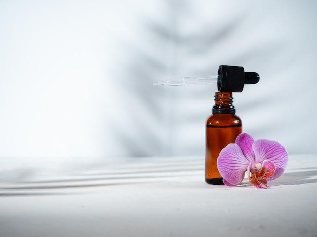 Frasco cosmético com um conta-gotas e uma flor de orquídea rosa em um fundo branco com sombras das plantas. spa, cosméticos e conceito de cuidados da pele. copyspace.