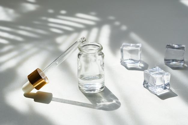 Frasco cosmético de essência com um conta-gotas e gelo em um fundo de sombras lindas palmeiras