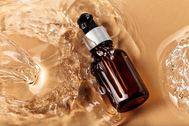 Frasco cosmético de óleo nas ondas de água, vista superior