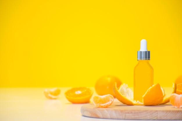 Frasco cosmético de soro de vitamina c em casca de tangerina com pedaços de laranja em fundo amarelo com espaço de cópia.